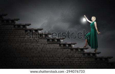 Young woman in green dress with lantern in darkness #294076733