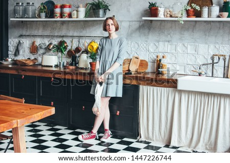 Young woman in grey dress with knitted rag bag string bag shopper in the kitchen, zero waste, slow life Photo stock ©