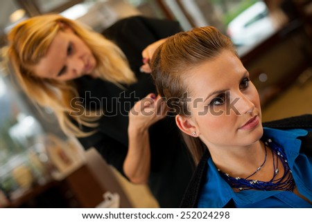 Young woman in hairdresser saloon having a haircut