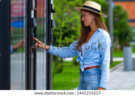 Young woman in hat buying soda, water and sweets in vending machine on the street during a walk in the city park