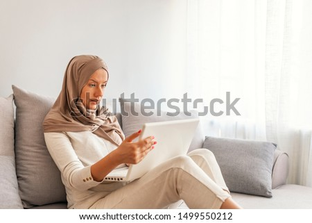Young woman in head scarf using laptop while sitting on couch. Expression of beautiful young woman wearing hijab working on laptop at living room. Working at home, online education, technology