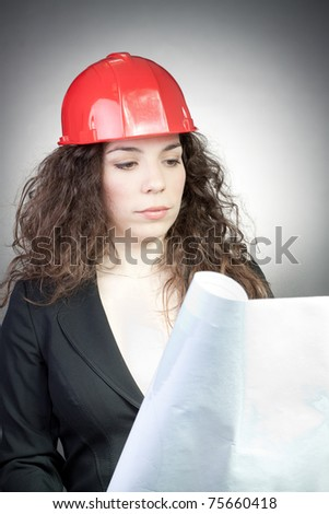 Young woman in helmet with blueprint, with grey background