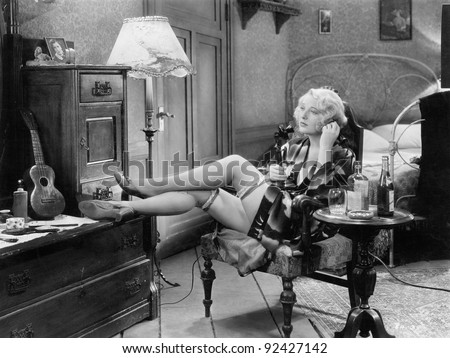 Young woman in her bedroom sitting on a chair with her legs on a dresser and a table with a few bottles of alcohol next to her