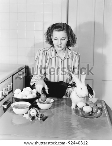 Young woman in her kitchen coloring Easter eggs