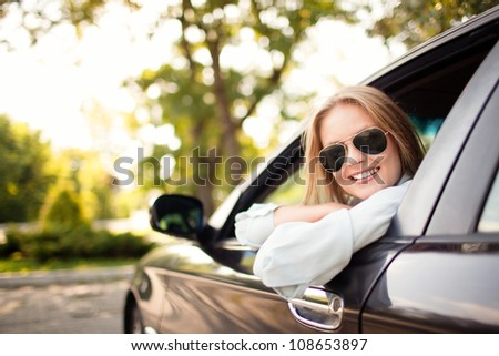 Young woman in her new car smiling.