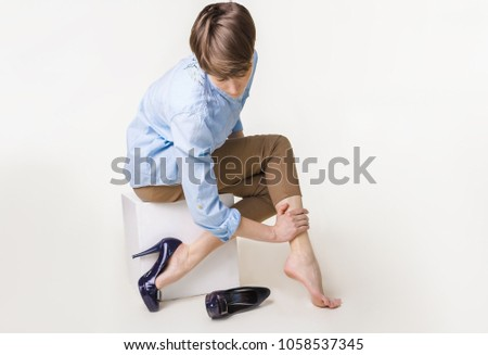 Young woman in high heels massaging her tired legs. Varicose veins concept. Painful varicose and spider veins on female legs.
