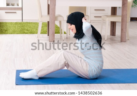 Young woman in hijab doing exercises at home