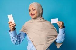 Young woman in hijab holding a white blank plastic card in her hand and texting on mobile phone in her other hand. Isolated on blue background with copy space
