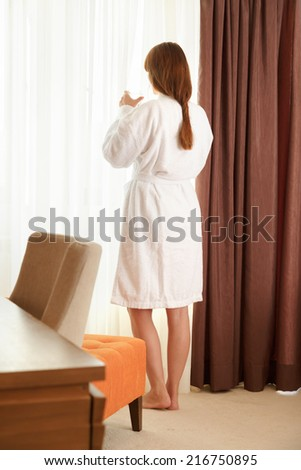 Young woman in hotel room drinking water