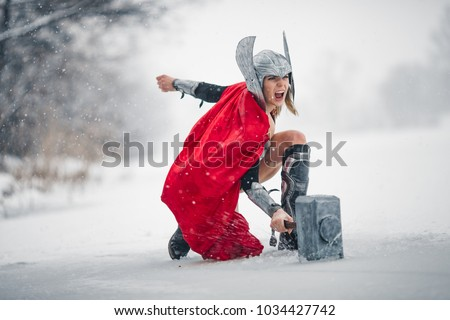 Young woman in image of Germanic-Scandinavian God of thunder and storm are striking with hammer in fury against winter forest background. Cosplay.
