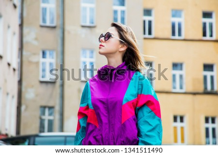 Young woman in jacket of 90s style stay at  back yard of house in East Europe