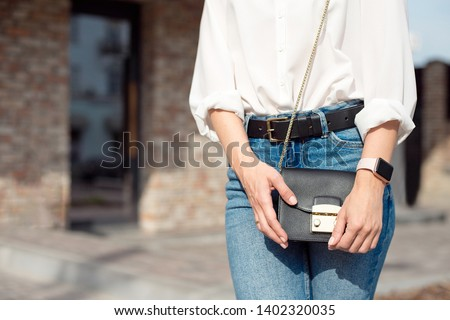 Young woman in jeans and a white shirt standing on the street holding a lady's bag in which lies her smart phone and wallet. Сток-фото ©