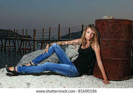 Young woman in jeans relaxing by Kameo island in Greece - stock photo
