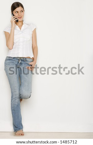 Young woman in jeans talking on cell phone