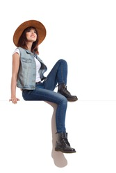 Young woman in jeans vest, black boots and brown suede hat is sitting on a top and looking away. Full length studio shot isolated on white.