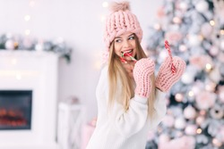 young woman in knitted clothes eats Christmas sweets. Christmas tree at home. close up.