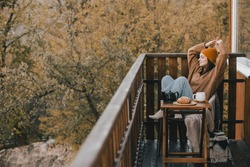 Young woman in knitted sweater and hat drinking tea and eating fresh croissants on cozy balcony of a wooden country house on autumn day.
