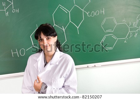 Young woman in lab coat standing next to chalkboard with chemical formula
