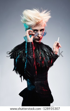 young woman in leather clothes holding her glasses and looking at camera while holding a cigarette in her other hand