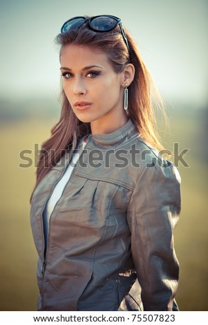 young woman in leather jacket and sunglasses outdoor portrait at sunset