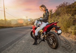 Young Woman in leather jacket and white pants sitting on high performance motorcyle on side of road looking at helmet at subset in trabuco canyon Ca