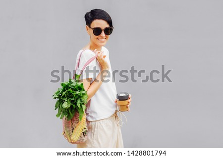 Young woman in light summer clothes with a eco bag of vegetables, greens and reusable coffee mug. Sustainable lifestyle. Eco friendly concept. #1428801794