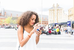 Young woman in London wandering and playing with augmented reality game on her smart phone. Blurred people on background.