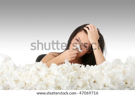 Young woman in lot of tissues around, ill