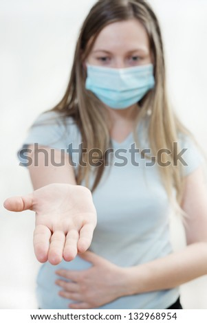 Young woman in medical mask. Focus on  hands. On white background.