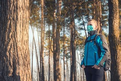 young woman in medical mask walks in a spring pinewood. Spring. safe walk. Coronavirus covid19