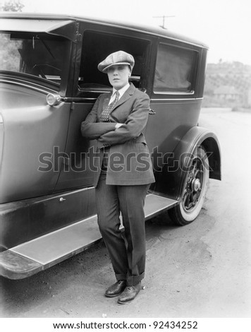 Young woman in men's clothing standing next to car