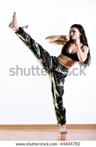 Young woman in military clothes kicking.