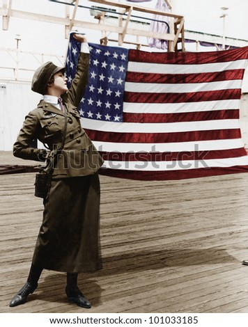 Young woman in military uniform holding up an American flag