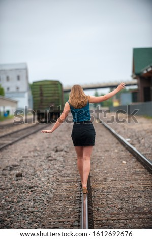 young woman in miniskirt walking away on rr tracks