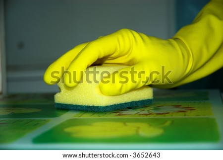 Young woman in muffles is washing table.