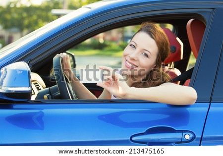 Young woman in new car showing blank drivers license or sign out, through side car window. Happy lovely female model driver enjoying her new auto outside parking lot. Positive face expression, emotion