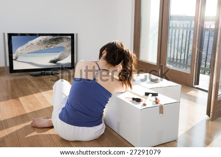 young woman in new house leaning on cardboard box and watching television