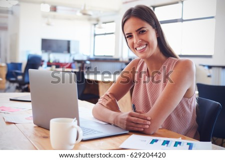 Young woman in office using laptop computer smiles to camera #629204420
