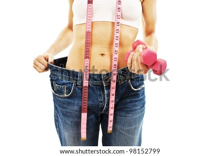 Young woman in old jeans pant after losing weight. Isolated on white background.