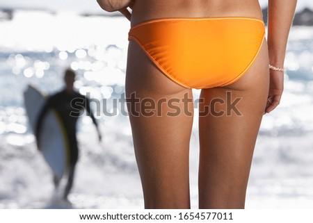 Young woman in orange bikini watching surfer in sea, back view
