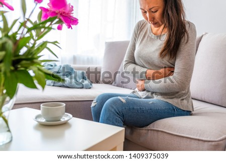 Young woman in pain lying on couch at home, casual style indoor shoot. Young woman with stomach ache sitting on bed. Young woman with stomach pain