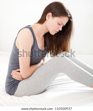 Young woman in pain sitting on bed, on white background