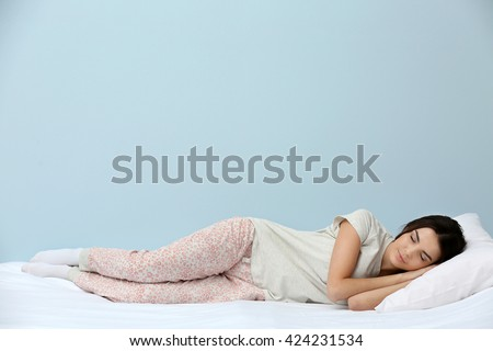 Young woman in pajamas sleeping on bed on blue background