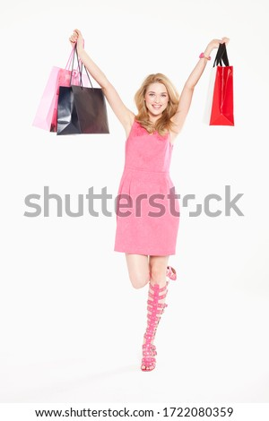 Young woman in pink dress and heels holding shopping bags, portrait