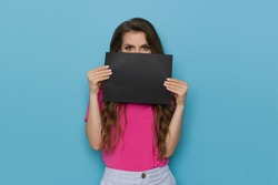 Young woman in pink shirt is hiding her face behind black sheet of paper. Waist up studio shot on blue background.