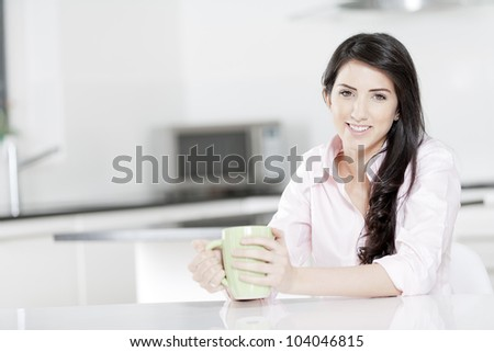 Young woman in pink shirt sitting at dining table at home drinking a hot drink.
