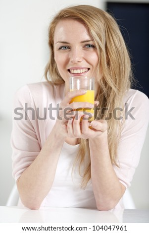 Young woman in pink shirt sitting at dining table at home with orange juice