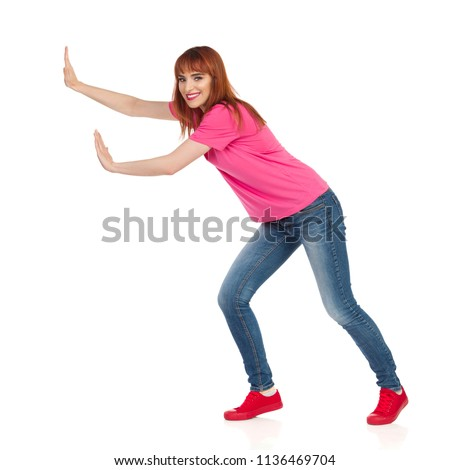 Young woman in pink t-shirt, jeans and red sneakers is standing with arms outstretched, pushing something and smiling. Side view. Full length studio shot isolated on white.