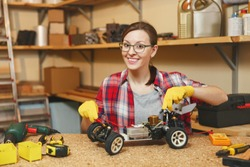 Young woman in plaid shirt, gray T-shirt, yellow gloves making toy car iron model constructor, working in carpentry workshop at wooden table place with different tools. Multimeter for electrician