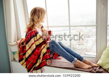 Young woman in plaid with cup of hot tea  sitting on windowsill #519923200